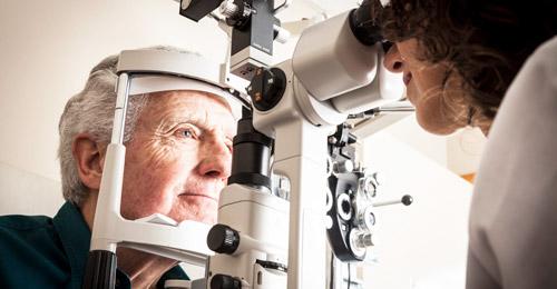 пожилой человек проверят зрение у врача