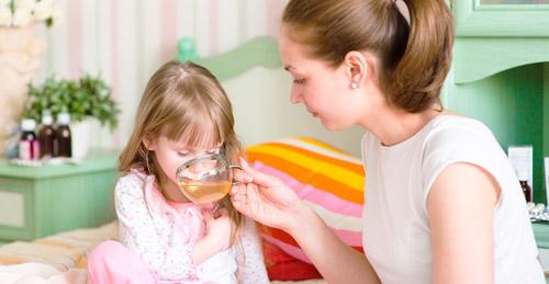 мама поит больного ребенка травяным чаем