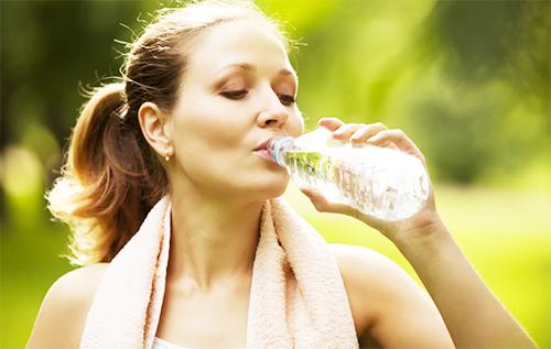 спортсменка пьет воду из пластиковой бутылки