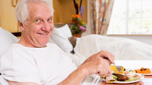 пожилой мужчина ест завтрак